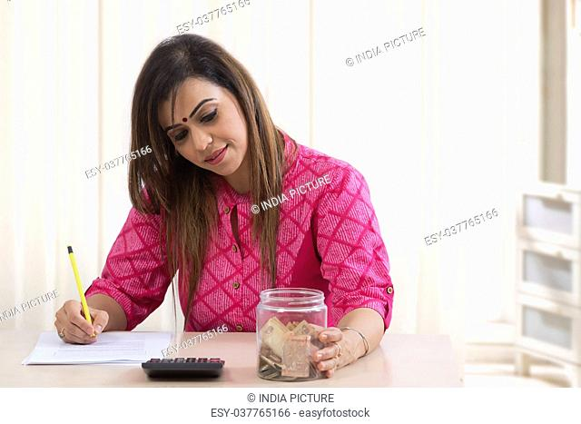 Woman with money box calculating bills