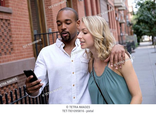 Couple looking at mobile phone during walk