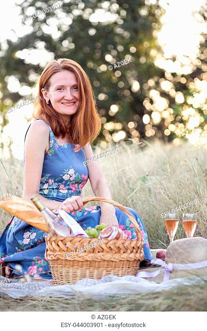 Summer - Provencal picnic in the meadow. girl smiling girl with a basket on a picnic