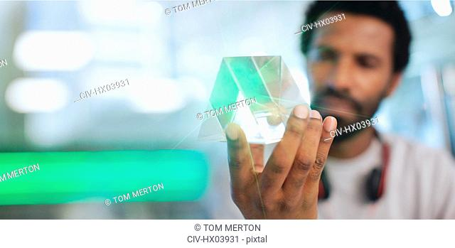 Close up innovative male entrepreneur examining glass triangle prototype