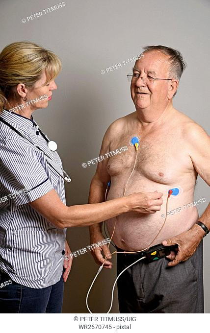England Uk Member of a Hospial Cardiac Measurement Team Installing A Ambulatory Ecg Monitor To An Overweight Male Patient