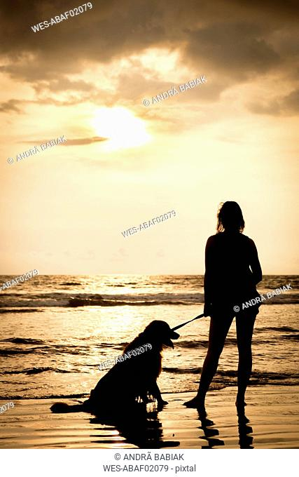 Mexico, Nayarit, silhouette of young woman with her dog on a leash at a beach at sunset