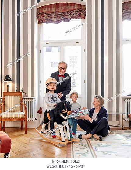 Grandparents and grandchildren with rocking horse and gift