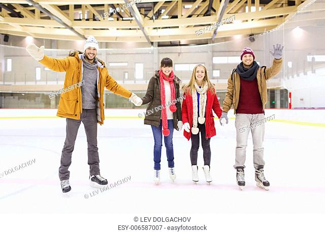 people, friendship, gesture, sport and leisure concept - happy friends waving hands on skating rink