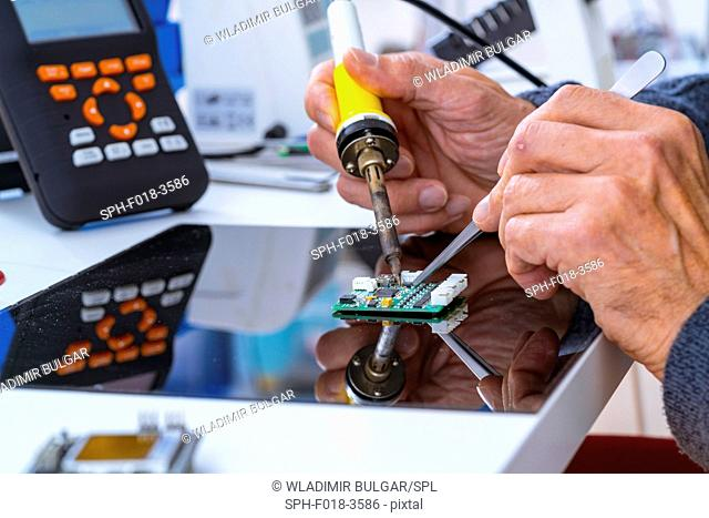 Person soldering an electronic component