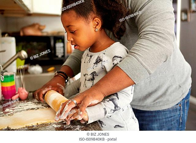 Father and daughter baking cookies together, mid section