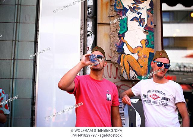 British tourists wear sunglasses and Russian military caps, they bought here from a souvenirs dealer, in front of the Berlin Wall Museum at Checkpoint Charlie...