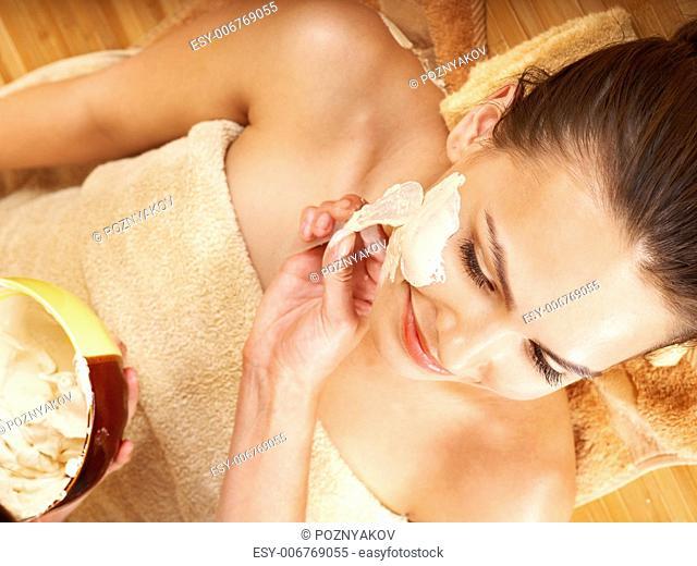 Beautiful girl having clay body mask apply by beautician