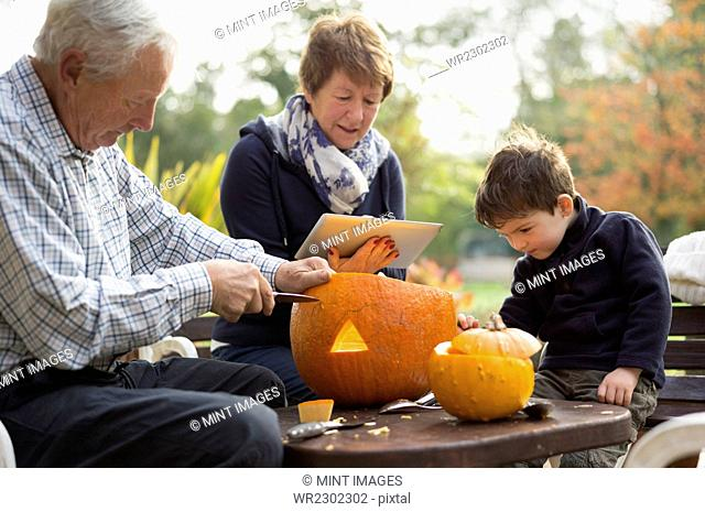 Two adults and a small child with large pumpkins, creating pumpkin lanterns for Halloween