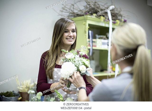 Smiling florist in flower shop presenting flower arrangement