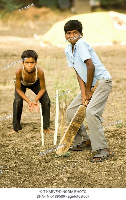 boys playing cricket Salunkwadi Maharashtra India Asia MR#TNK001