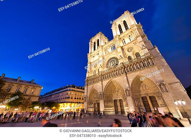 PARIS - JUNE 2014: Notre Dame Cathedral at night with tourists. Notre Dame is visited by 12 million people every year