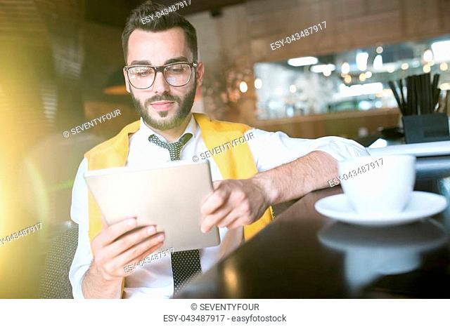 Warm toned portrait of handsome bearded businessman wearing glasses using digital tablet while enjoying coffee break in cafe behind glass wall in sunlight