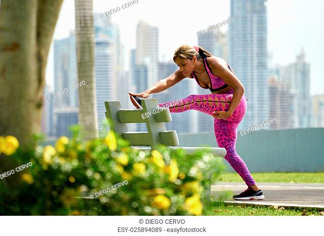 Young african american woman warming up before starting her daily sport routine. The girl trains at early morning along the Cinta Costera in Panama