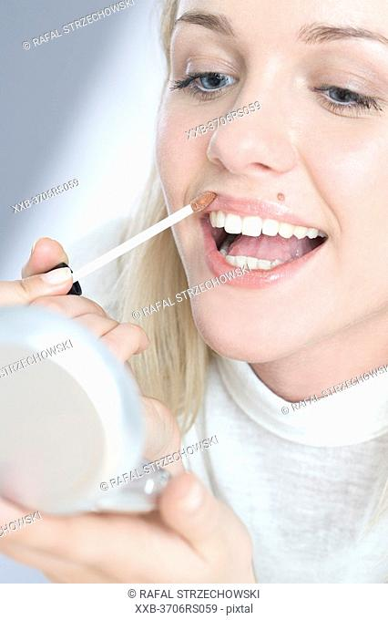 young woman using lipliner
