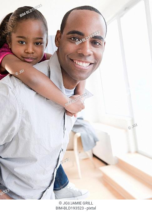 African American father carrying daughter on back