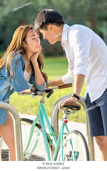 Korean couple locking bicycle to rack in park