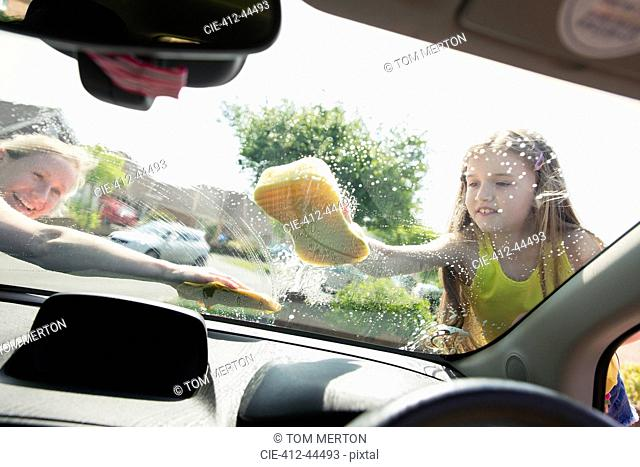 Mother and daughter washing car windshield