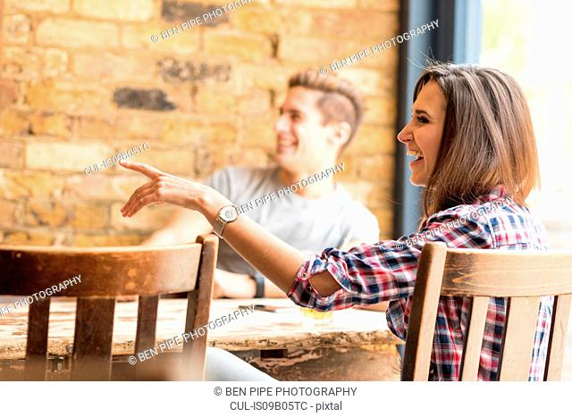 Young couple pointing in bar