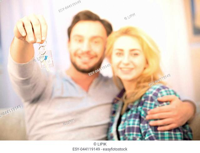 Toned of happy couple in love showing key from new apartment. Young couple happy smiling for camera after signing agreement for purchase or sale