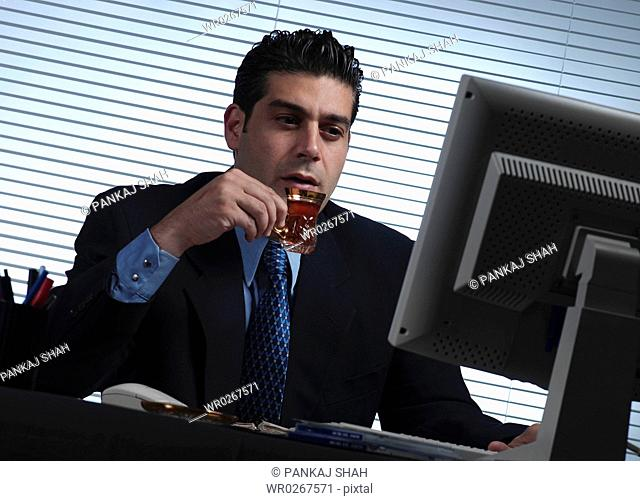 Businessman having his tea in office