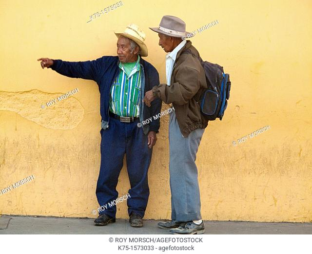 Two Guatemalan men chatting and pointing
