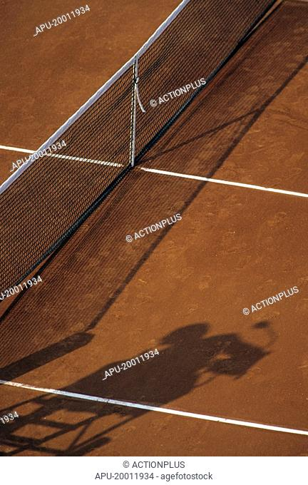 Tennis net in a clay court with umpires chair shadow