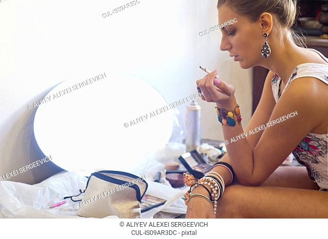 Young woman smoking cigarette, surrounded by cosmetics and mirror