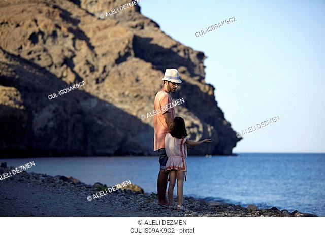 Father and daughter standing by the sea, Costa Brava, Catalonia, Spain