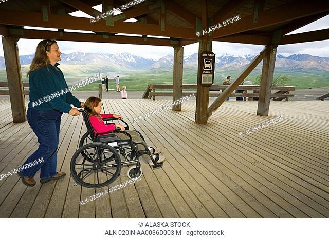 A mother pushes her daughter in wheelchair on a handicap accessable viewing deck Denali NP Alaska