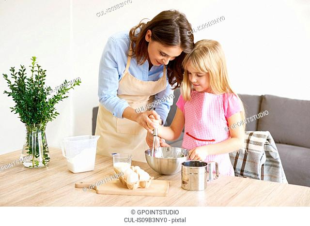 Mother helping daughter whisk ingredients together in bowl