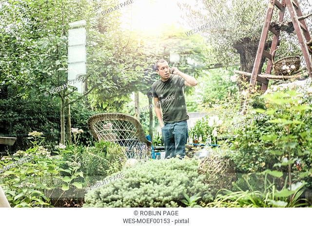 Man talking on smartphone in garden
