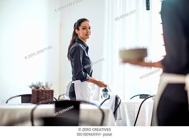 Waitresses setting table in restaurant