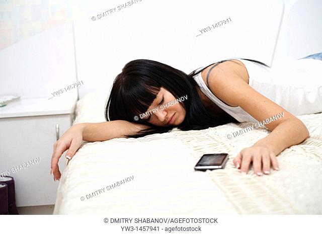Pretty brunette woman sleeping on bed with cell phone