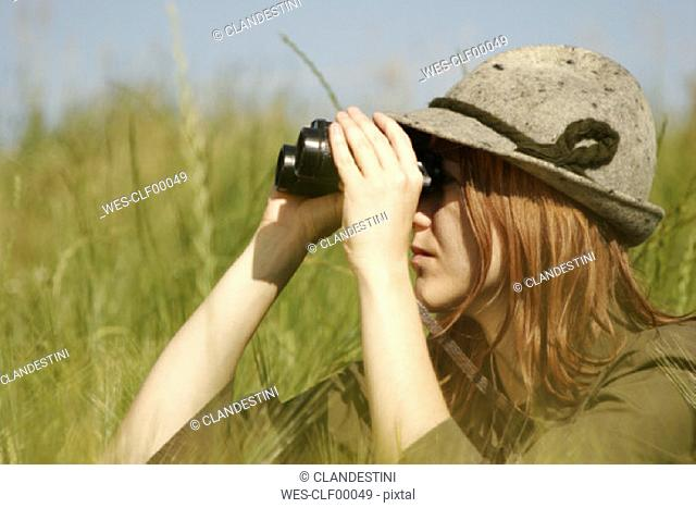 Young woman using binoculars in field