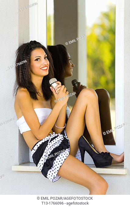 Skinny young woman tucked on a window frame with a microphone in hand