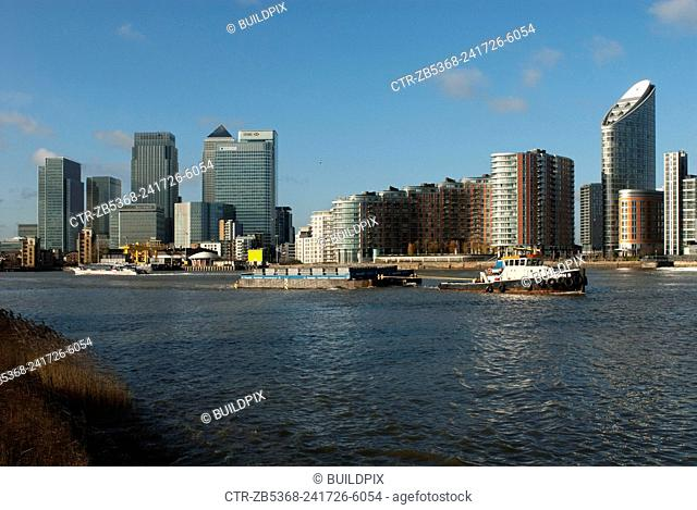 A barge pulled on the Thames near Canary Wharf, Docklands, East London, UK