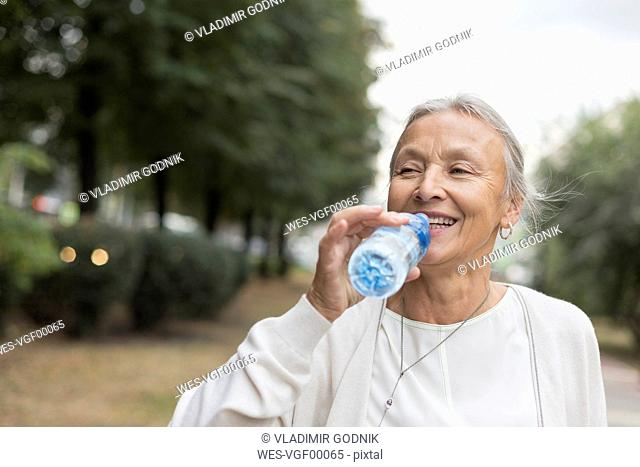 Happy senior woman outdoors drinking water from bottle