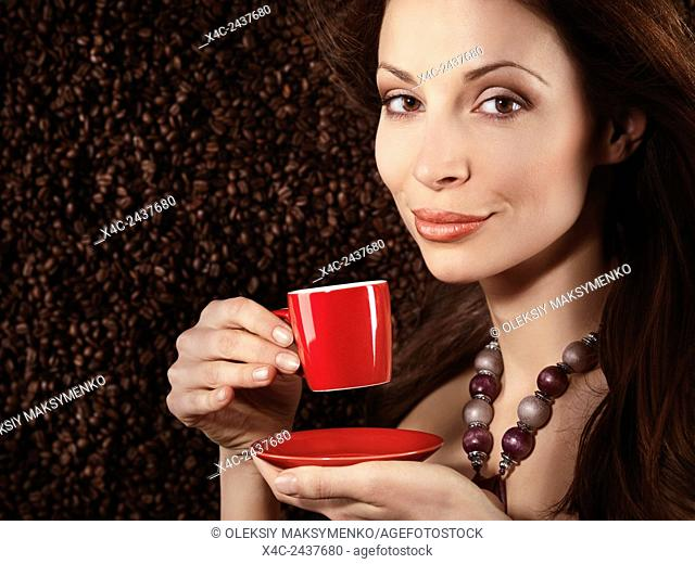 Beautiful young smiling woman holding a red cup of espresso coffee with arabica coffe beans background behind her