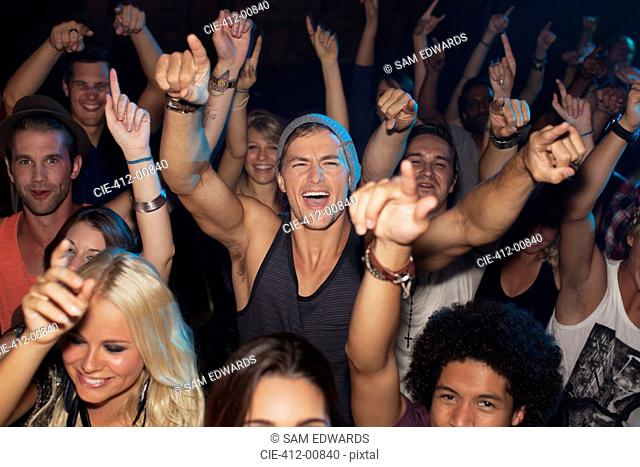 Enthusiastic man cheering in crowd at concert