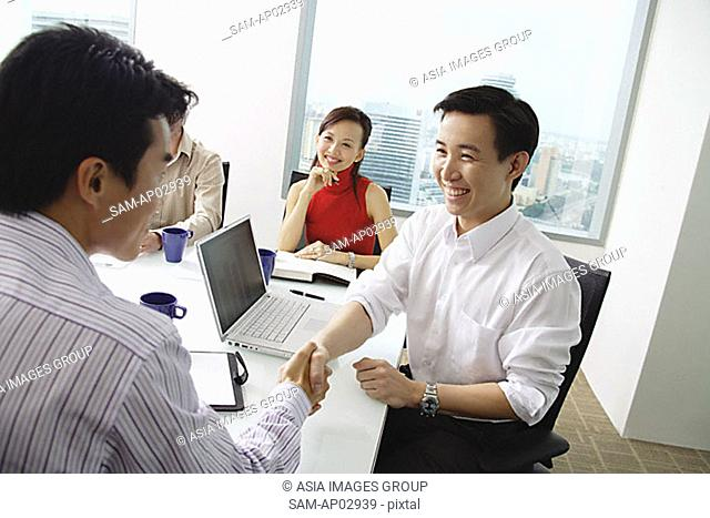 Two businessmen exchanging business cards, woman looking at them