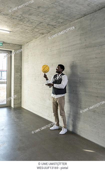 Businessman balancing basketball on office floor