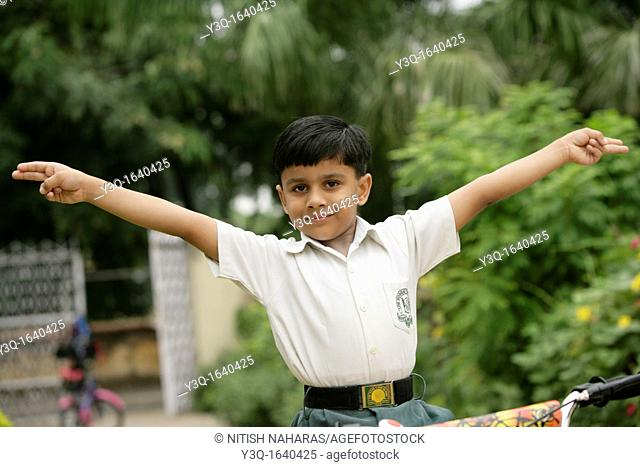 Young Indian school boy expressing elation with arms raised as if he is flying