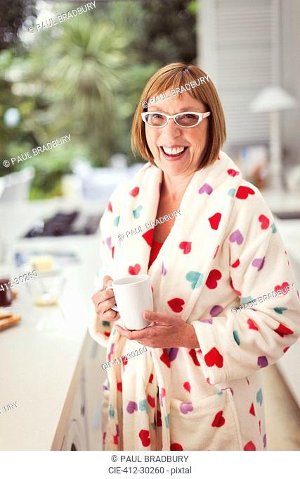 Portrait smiling mature woman drinking coffee in bathrobe