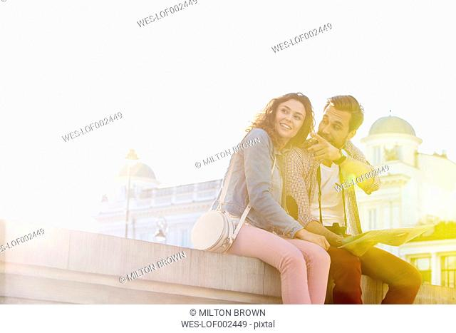 Poland, Warsaw, young couple with camera and city map having a rest