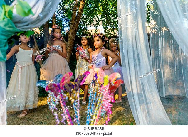 Group of young girls dressed as fairies, playing outdoors