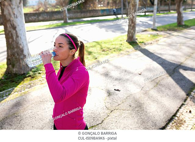 Young woman in street drinking water from water bottle