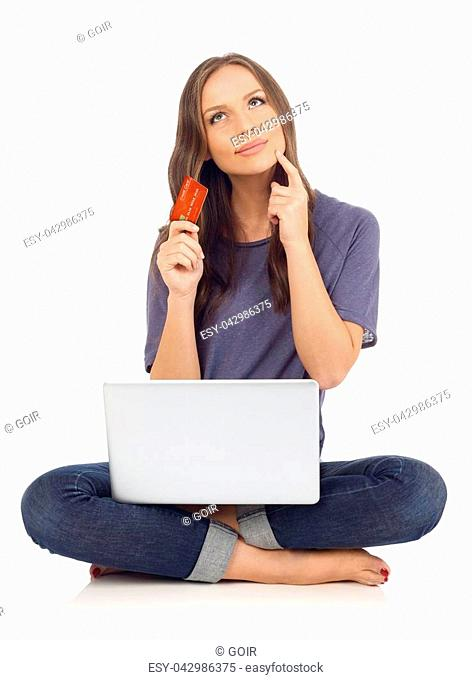 Teenager holding a credit card and a laptop and thinking, white background