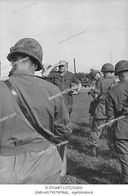 A United States Army serviceman addressing a group of other soldiers, he is holding his helmet and shielding his eyes from the sun while addressing the group of...
