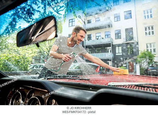 Smiling mature man washing his car